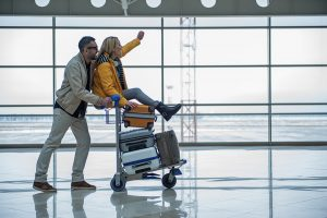 couple on luggage cart in airport